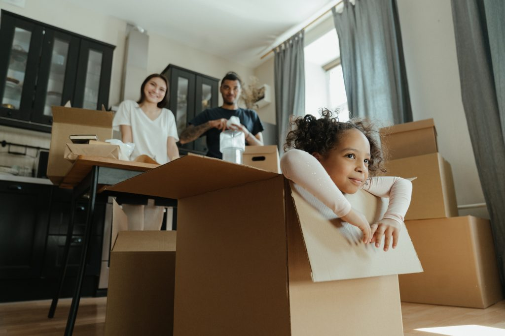 girl-playing-in-box-kitchen-smiling-parents